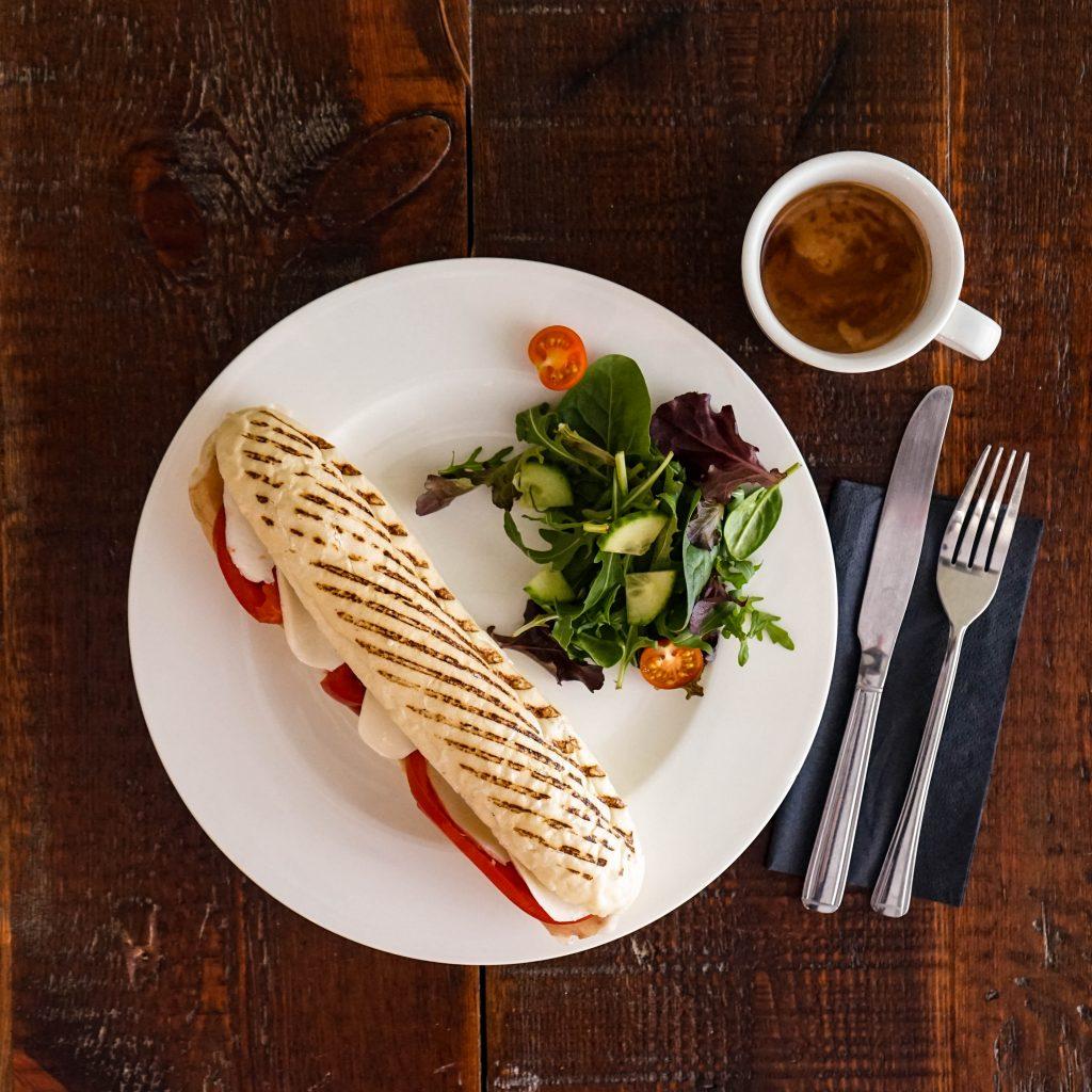 beautiful dish of Italian mozzarella and tomato panini with side of salad and coffee next to it in a small Italian mug